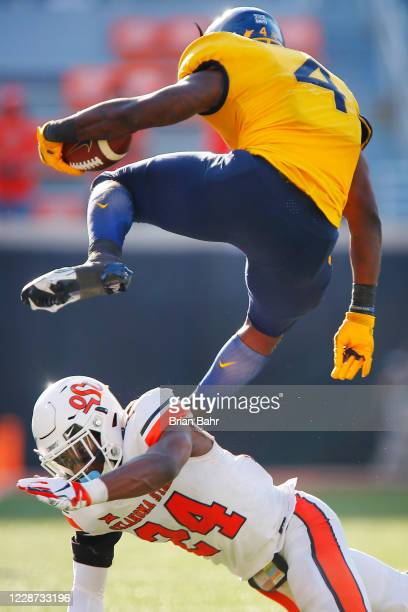 Running back Leddie Brown of the West Virginia Mountaineers hurdles over cornerback Jarrick Bernard-Converse of the Oklahoma State Cowboys for a...