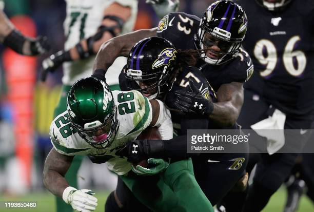 Running back Le'Veon Bell of the New York Jets is tackled by the defense of middle linebacker Josh Bynes and defensive end Jihad Ward of the...