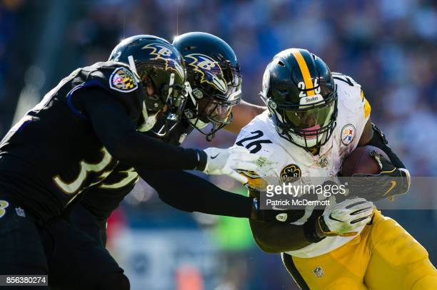 Running back Le'Veon Bell of the Pittsburgh Steelers carries the ball against defensive back Marlon Humphrey and linebacker Tyus Bowser of the...