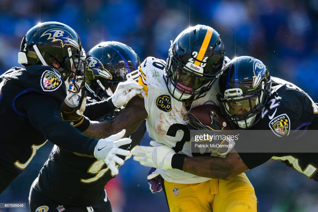 Running back Le'Veon Bell #26 of the Pittsburgh Steelers is tackled by defensive end Za'Darius Smith #90 and cornerback Jimmy Smith #22 of the Baltimore Ravens in the fourth quarter at M&T Bank Stadium on October 1, 2017 in Baltimore, Maryland.