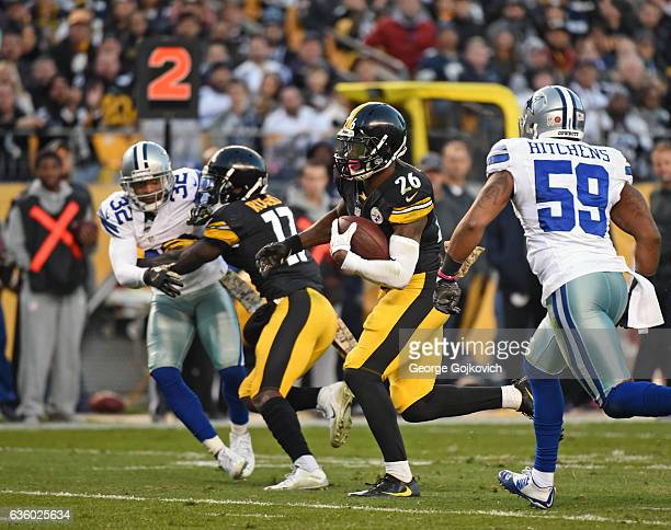 Running back Le'Veon Bell of the Pittsburgh Steelers runs with football as he is pursued by linebacker Anthony Hitchens of the Dallas Cowboys and as...