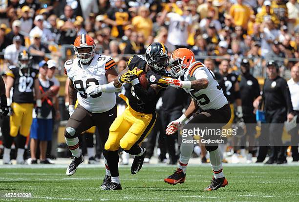 Running back Le'Veon Bell of the Pittsburgh Steelers runs with the football as he is pursued by defensive linemen Armonty Bryant and Billy Winn of...