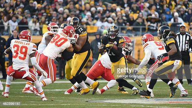 Running back Le'Veon Bell of the Pittsburgh Steelers runs with the football as offensive lineman Ramon Foster blocks linebacker Josh Mauga of the...