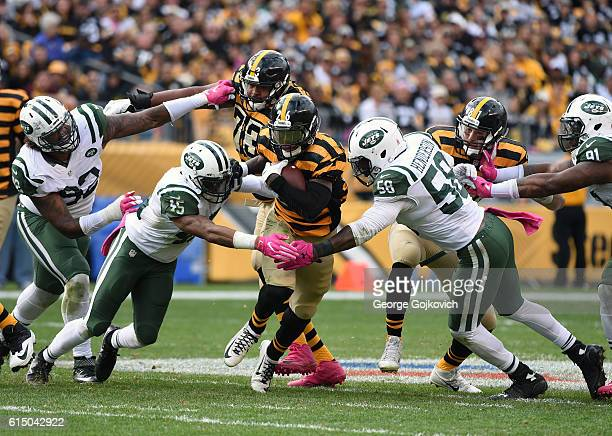 Running back Le'Veon Bell of the Pittsburgh Steelers runs with the football as offensive guard Ramon Foster and tight end Jesse James block against...