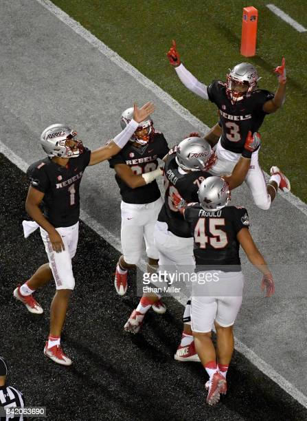 Running back Lexington Thomas of the UNLV Rebels celebrates in the end zone with teammates including quarterback Armani Rogers after scoring on a...