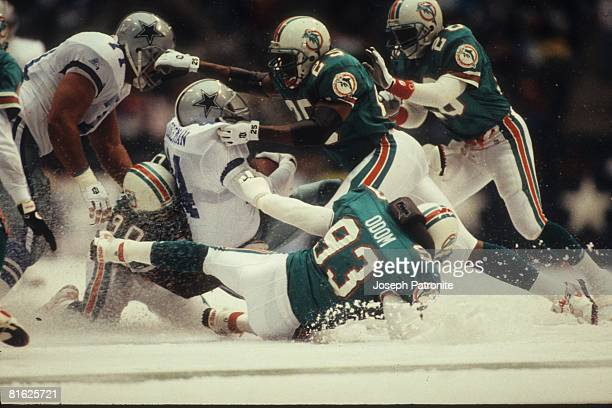 Running back Lincoln Coleman of the Dallas Cowboys is wrapped up by the Miami Dolphins defense at Texas Stadium on November 25 1993 in Irving Texas...