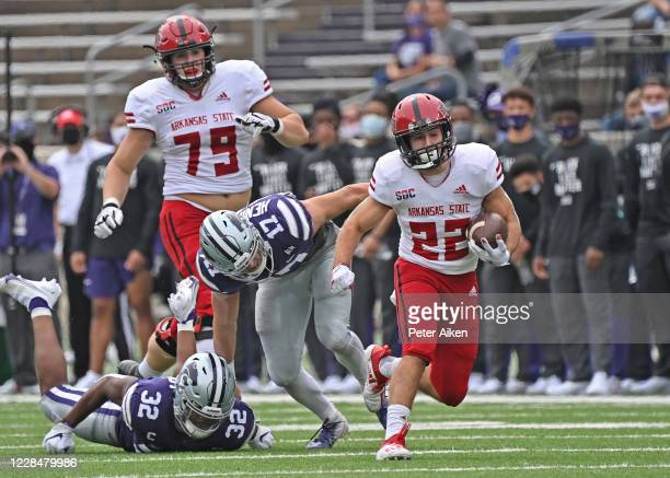Running back Lincoln Pare of the Arkansas State Red Wolves rushes up field against defensive back Jonathan Alexander of the Kansas State Wildcats...