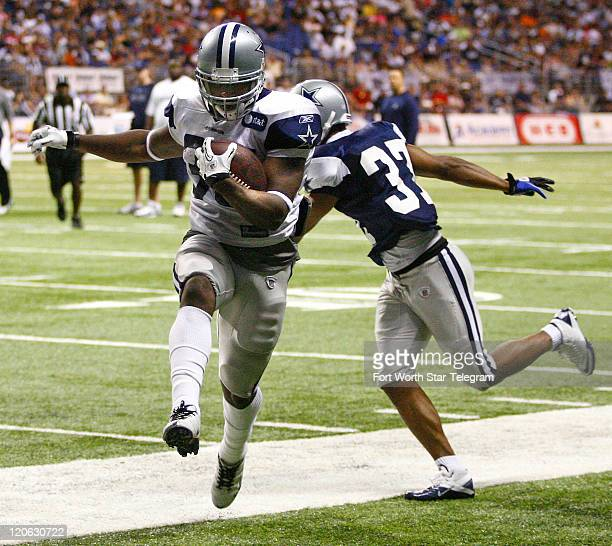 Running back Lonyae Miller is forced out of bounds by corner back Bryan McCann during the Dallas Cowboys blue/white scrimmage at the Alamodome in San...