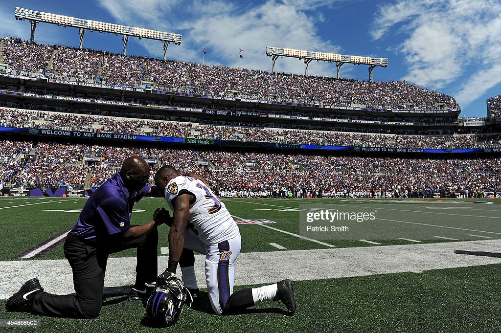 Running back Lorenzo Taliaferro #34 of the Baltimore Ravens prays with a coach prior to playing the Cincinnati Bengals at M&T Bank Stadium on September 7, 2014 in Baltimore, Maryland.