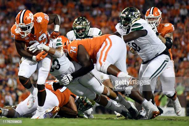 Running back Lyn-J Dixon of the Clemson Tigers rushes after contact from linebacker Jaylon Sharpe of the Charlotte 49ers during their football game...
