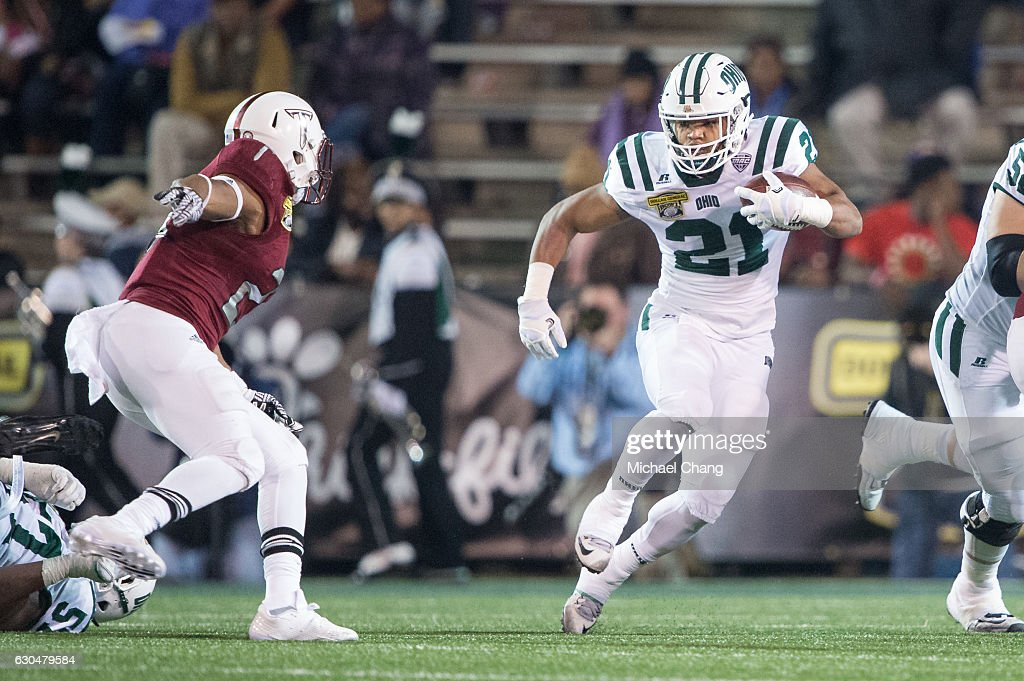 Running back Maleek Irons #21 of the Ohio Bobcats looks to maneuver by linebacker William Lloyd #23 of the Troy Trojans on December 23, 2016 in Mobile, Alabama.