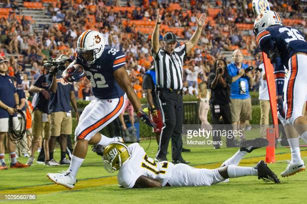 Running back Malik Miller of the Auburn Tigers scores a touchdown in front of defensive back Joshua Fisher of the Alabama State Hornets during the...
