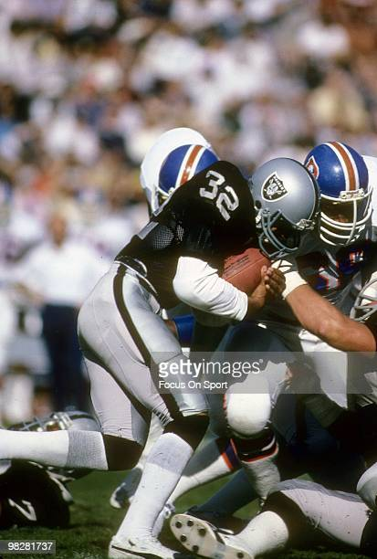 LOS ANGELES CA CIRCA 1980' Running Back Marcus Allen of the Los Angeles Raiders plays carries the ball against the Denver Broncos circa mid 1980's...