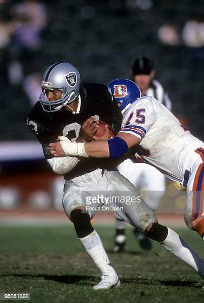 LOS ANGELES CA CIRCA 1980' Running Back Marcus Allen of the Los Angeles Raiders plays is his by defensive end Rulon Jones of the Denver Broncos circa...