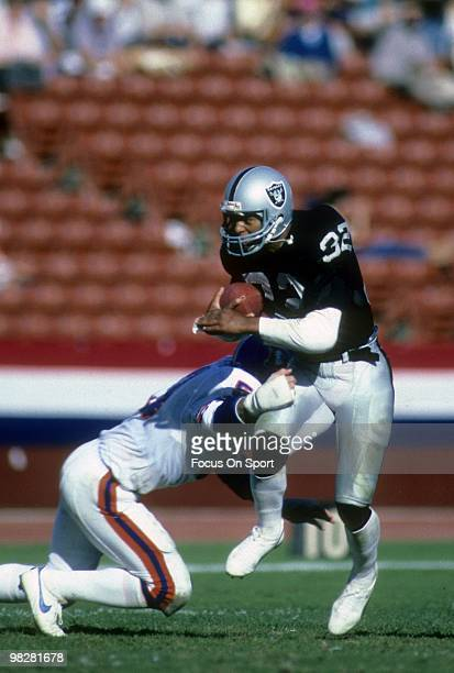 LOS ANGELES CA CIRCA 1980' Running Back Marcus Allen of the Los Angeles Raiders tries to run through the tackle of linebacker Randy Gradishar of the...