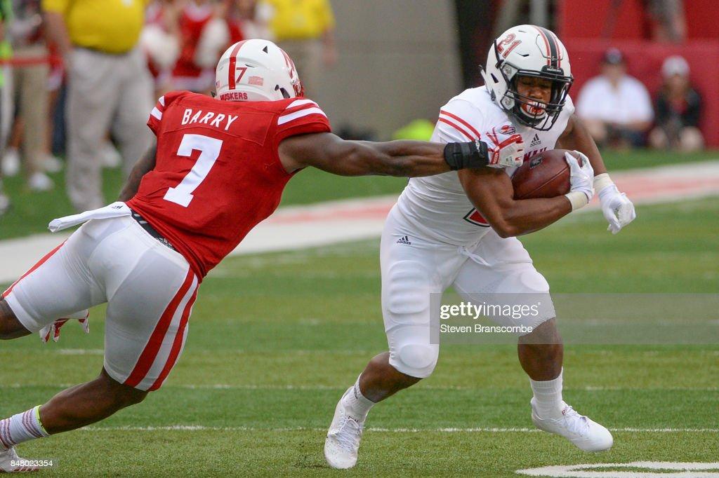 Running back Marcus Jones #21 of the Northern Illinois Huskies attempts to avoid the tackle of linebacker Mohamed Barry #7 of the Nebraska Cornhuskers at Memorial Stadium on September 16, 2017 in Lincoln, Nebraska.