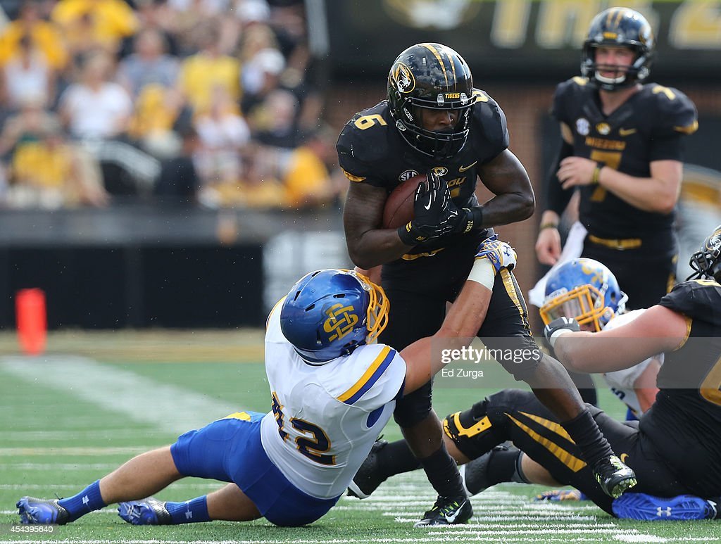 Running back Marcus Murphy #6 of the Missouri Tigers is tackled by Nick Mears #42 of the South Dakota State Jackrabbits in the first quarter at Memorial Stadium on August 30, 2014 in Columbia, Missouri.