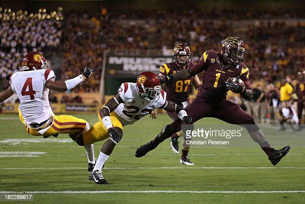 Running back Marion Grice of the Arizona State Sun Devils rushes the football past cornerback Torin Harris and safety Leon McQuay III of the USC...