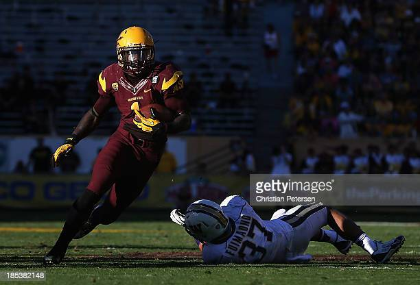 Running back Marion Grice of the Arizona State Sun Devils rushes the football past linebacker Princeton Fuimaono of the Washington Huskies during the...