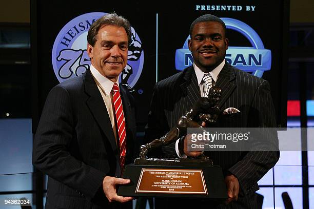 Running back Mark Ingram of the Alabama Crimson Tide poses with Head coach Nick Saban and the Heisman Trophy during a press conference after being...