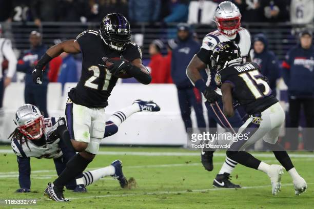 Running back Mark Ingram II of the Baltimore Ravens rushes past cornerback Stephon Gilmore of the New England Patriots in the first half at M&T Bank...