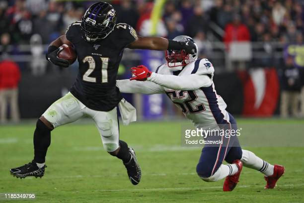 Running back Mark Ingram II of the Baltimore Ravens rushes past linebacker Elandon Roberts of the New England Patriots during the fourth quarter at...