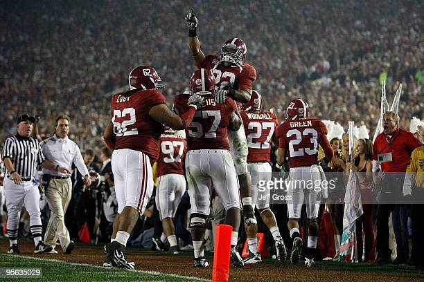 Running back Mark Ingram jumps on lineman Marcell Dareus of the Alabama Crimson Tide as they celebrate with teammates after Dareus' 28yard...