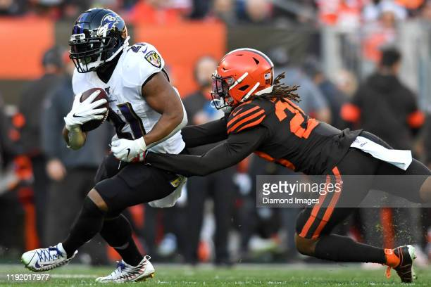 Running back Mark Ingram of the Baltimore Ravens breaks the tackle of defensive back Sheldrick Redwine of the Cleveland Browns in the third quarter...