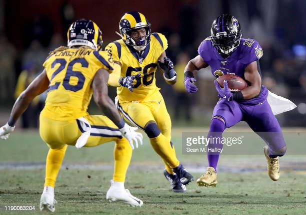 Running back Mark Ingram of the Baltimore Ravens carries the ball against the defense of the Los Angeles Rams during the game at Los Angeles Memorial...