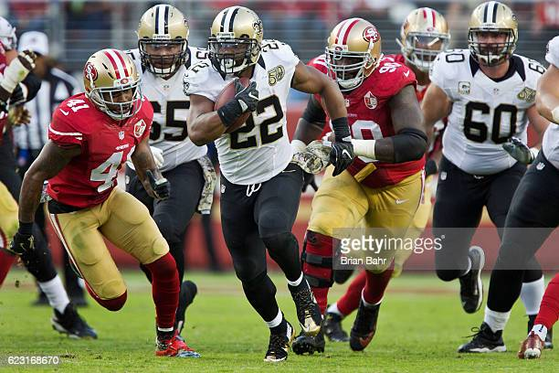 Running back Mark Ingram of the New Orleans Saints carries the ball for a 14yard gain against safety Antoine Bethea and defensive lineman Glenn...
