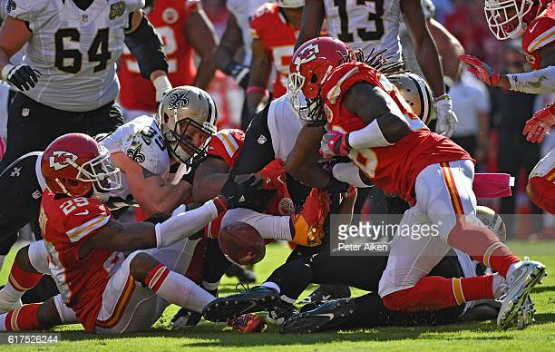 Running back Mark Ingram of the New Orleans Saints fumbles the ball as defensive back Ron Parker of the Kansas City Chiefs punches the ball lose...