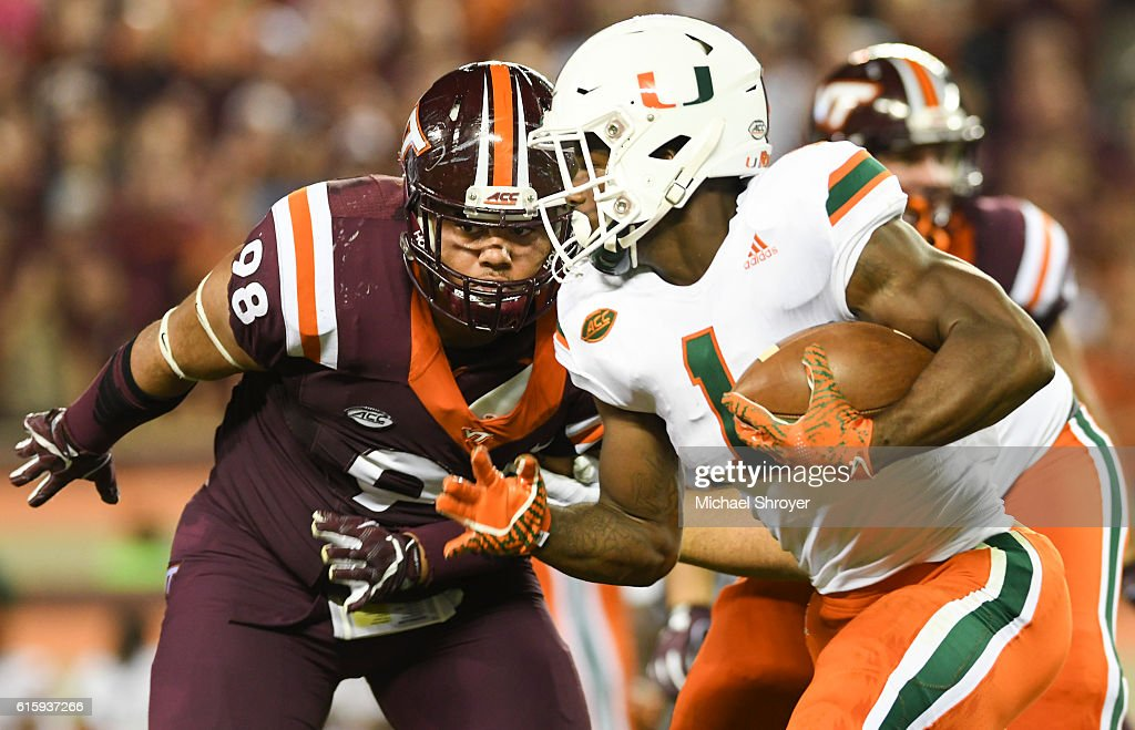 Running back Mark Walton #1 of the Miami Hurricanes carries the ball while being pursued by defensive tackle Ricky Walker #98 of the Virginia Tech Hokies in the first half at Lane Stadium on October 20, 2016 in Blacksburg, Virginia.