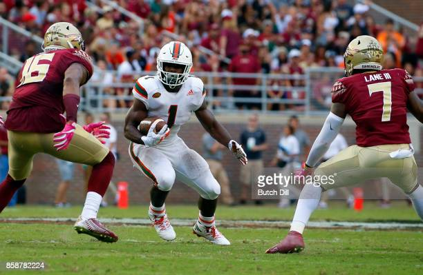 Running back Mark Walton of the Miami Hurricanes looks for a hole to run through as linebacker Jacob Pugh and defensive back Ermon Lane of the...