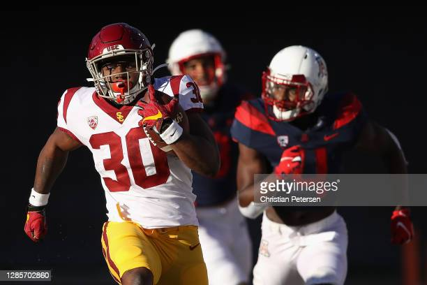 Running back Markese Stepp of the USC Trojans rushes the football for 49 yards past defensive back Christian Roland-Wallace of the Arizona Wildcats...