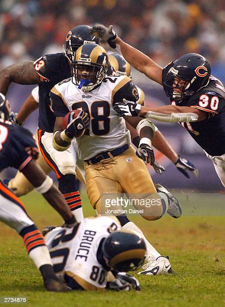 Running back Marshall Faulk of the St Louis Rams breaks away from safety Mike Brown of the Chicago Bears during a game on November 16 2003 at Soldier...
