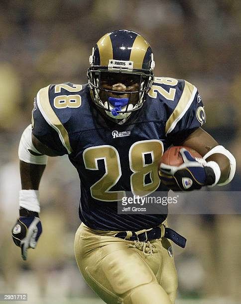 Running back Marshall Faulk of the St Louis Rams carries the ball during the NFC Divisional Playoff game against the Carolina Panthers on January 10...