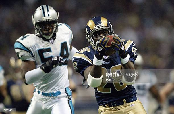 Running back Marshall Faulk of the St. Louis Rams catches a pass in front of linebacker Will Witherspoon of the Carolina Panthers during the NFC...