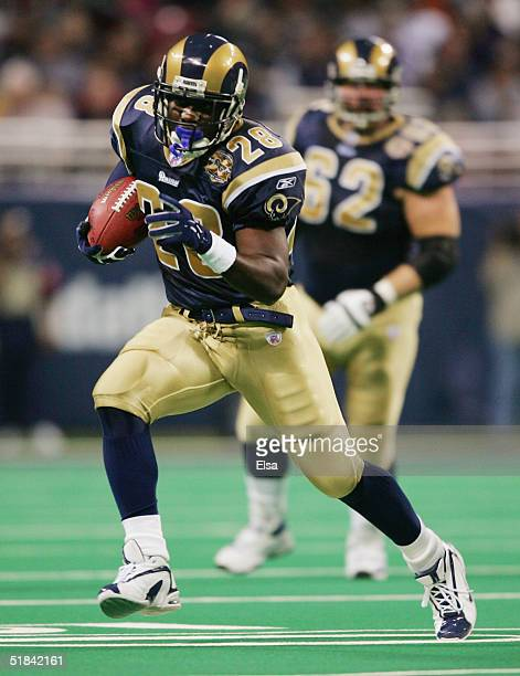 Running back Marshall Faulk of the St. Louis Rams runs upfield against the New England Patriots on November 7, 2004 at the Edward Jones Dome in St....