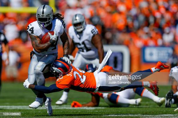 Running back Marshawn Lynch of the Oakland Raiders is hit by defensive back Darian Stewart of the Denver Broncos during the first quarter of a game...
