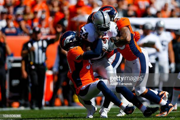 Running back Marshawn Lynch of the Oakland Raiders is hit by defensive back Justin Simmons and linebacker Von Miller of the Denver Broncos during a...