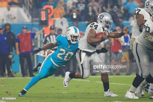 Running back Marshawn Lynch of the Oakland Raiders is tackled by free safety Reshad Jones of the Miami Dolphins at Hard Rock Stadium on November 5...