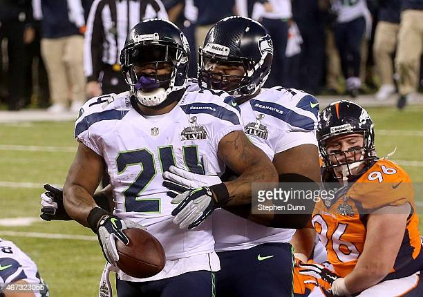 Running back Marshawn Lynch of the Seattle Seahawks celebrates his 1yard touchdown with teammate tackle Alvin Bailey in the second quarter against...