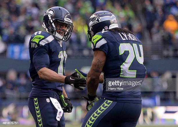 Running back Marshawn Lynch of the Seattle Seahawks celebrates with wide receiver Percy Harvin after Lynch scores on a 15-yard run in the second...