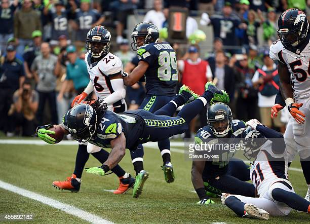 Running back Marshawn Lynch of the Seattle Seahawks dives int the end zone over cornerback Aqib Talib of the Denver Broncos for the game winning...