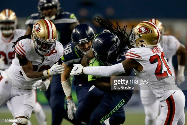 Running back Marshawn Lynch of the Seattle Seahawks is tackled by free safety Jimmie Ward of the San Francisco 49ers during the game at CenturyLink...