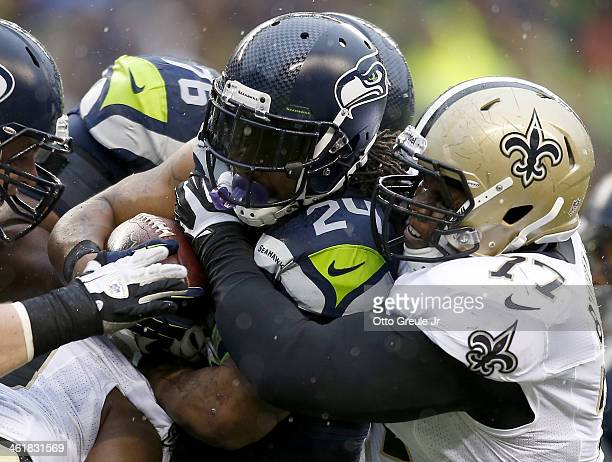 Running back Marshawn Lynch of the Seattle Seahawks runs the ball as he is hit by nose tackle Brodrick Bunkley of the New Orleans Saints in the...