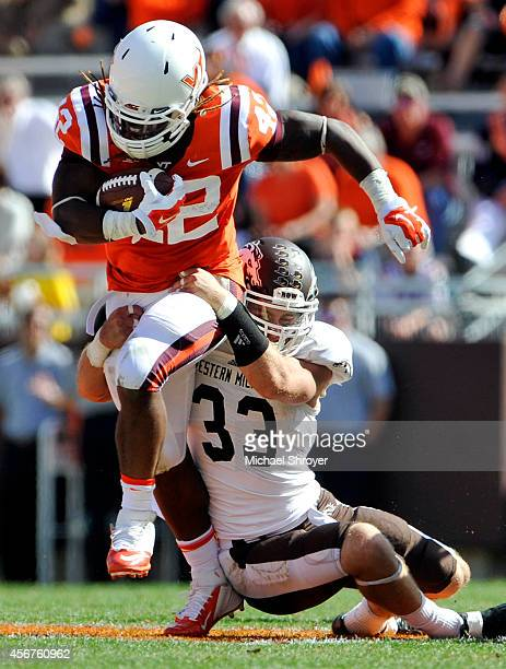 Running back Marshawn Williams of the Virginia Tech Hokies is tackled by strong safety Justin Currie of the Western Michigan Broncos in the second...