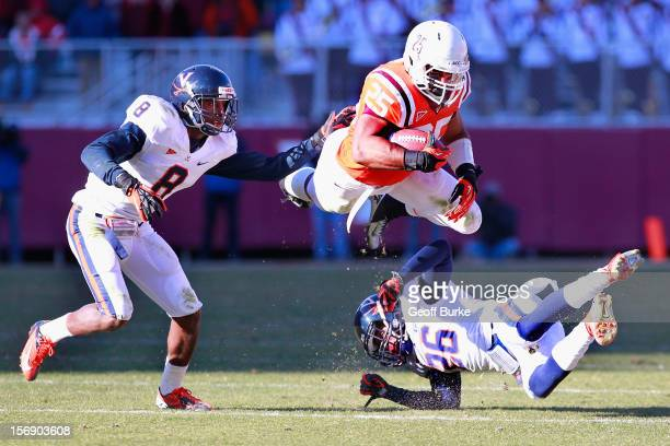 Running back Martin Scales of the Virginia Tech Hokies leaps while running with the ball to avoid safety Anthony Harris of the Virginia Cavaliers and...