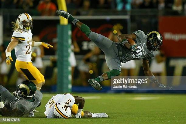 Running back Marvin Kinsey Jr #25 of the Colorado State Rams gets upended by cornerback Rico Gafford of the Wyoming Cowboys during the second quarter...