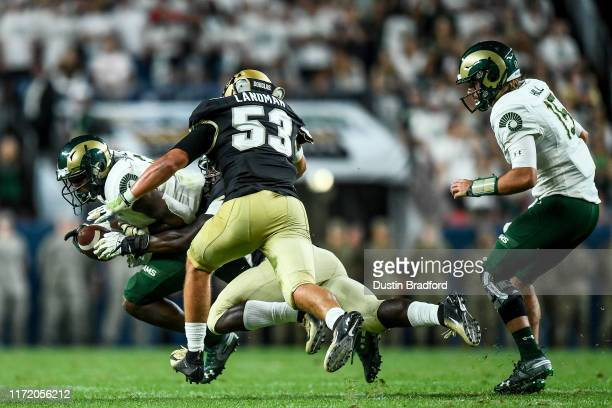 Running back Marvin Kinsey Jr #5 of the Colorado State Rams is tackled for a loss by linebacker Davion Taylor and linebacker Nate Landman of the...